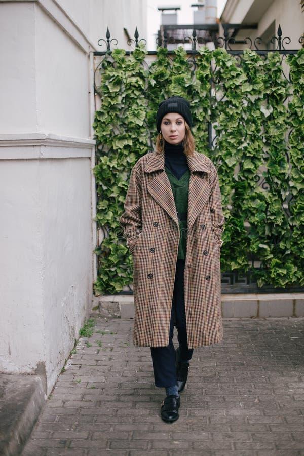 Bärande modekläder för ung härlig kvinna som poserar på gatan fotografering för bildbyråer