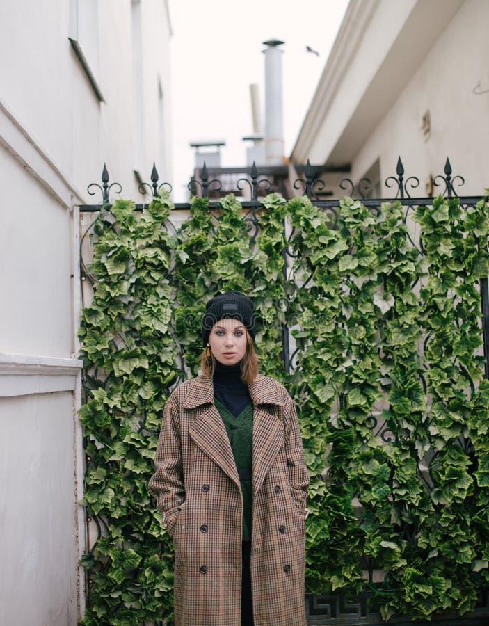 Bärande modekläder för ung härlig kvinna som poserar på gatan royaltyfri bild
