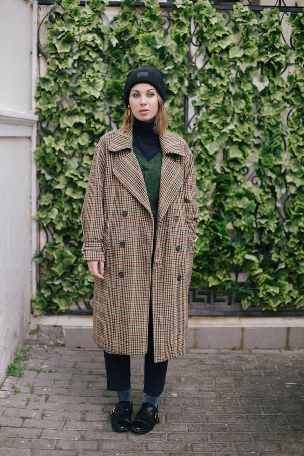 Bärande modekläder för ung härlig kvinna som poserar på gatan royaltyfria foton
