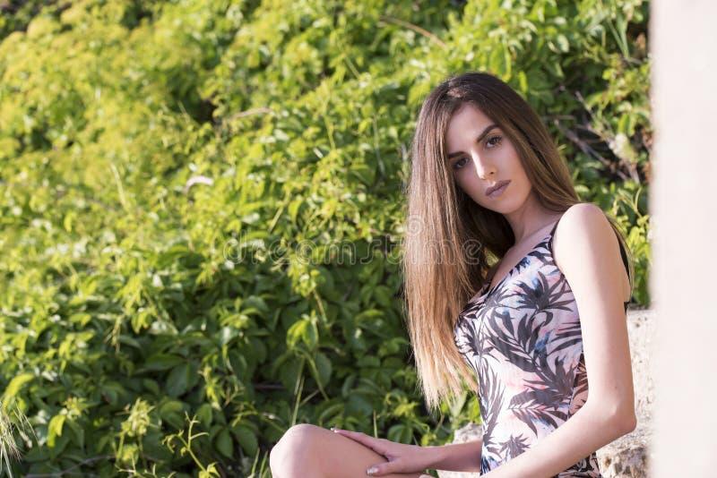 Bärande monokini för slank kvinna som sitter på trappa royaltyfri foto