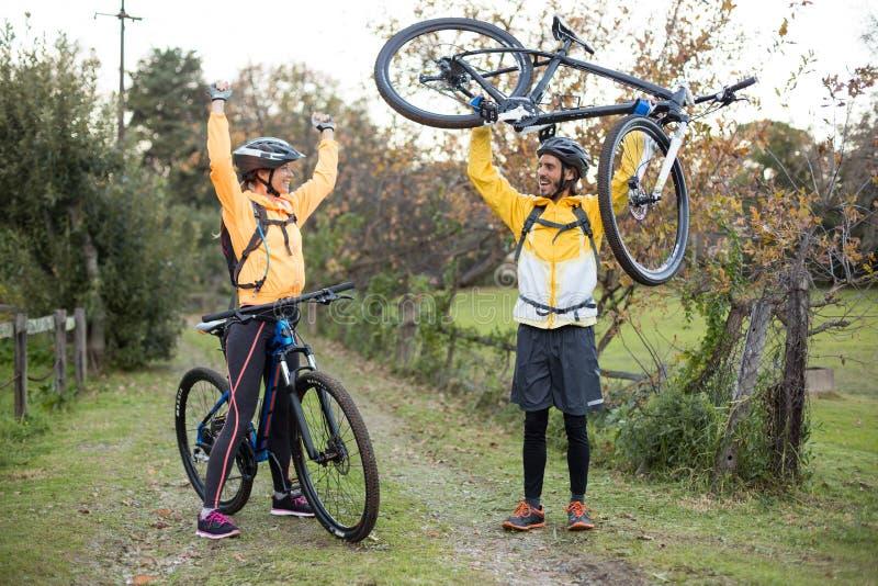 Bärande mountainbike för manlig cyklist medan kvinnlig cyklist som hurrar honom royaltyfri foto