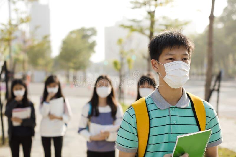 Bärande munmaskering för student mot smog i stad royaltyfri fotografi