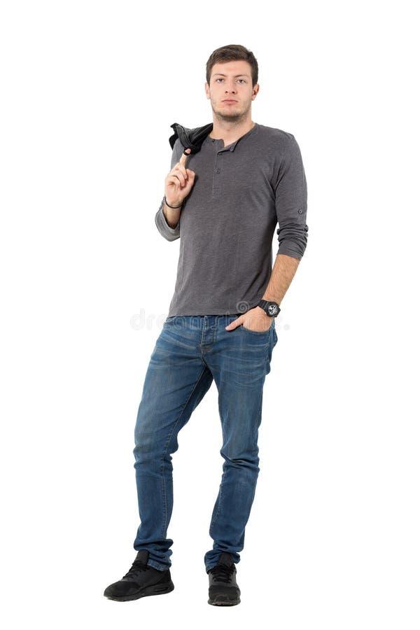 Bärande omslag för stilig tillfällig man över skuldran som ser kameran fotografering för bildbyråer
