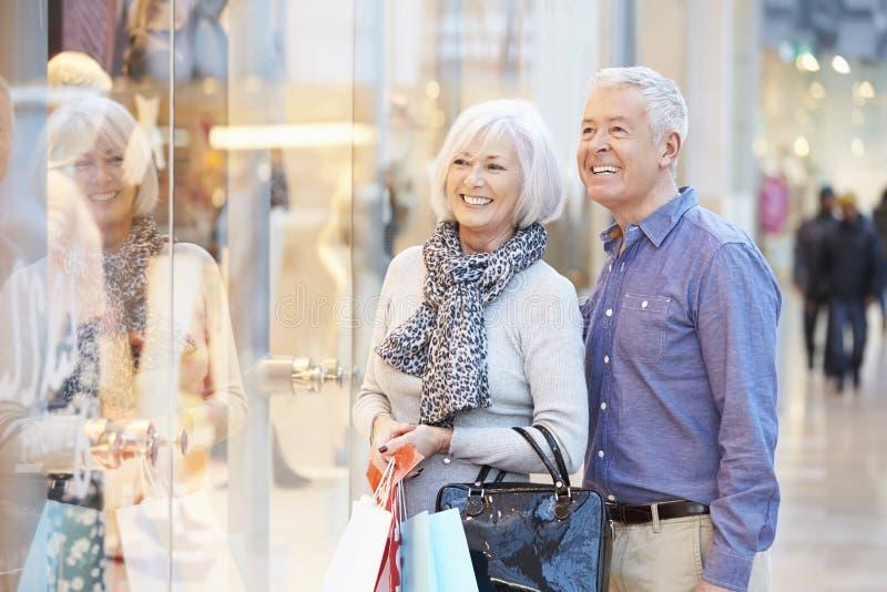 Bärande påsar för lyckliga höga par i shoppinggalleria royaltyfri bild