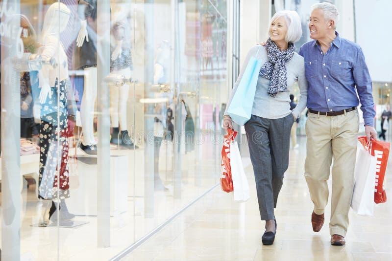 Bärande påsar för lyckliga höga par i shoppinggalleria royaltyfria bilder