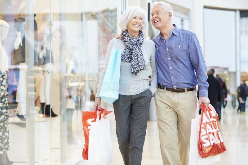 Bärande påsar för lyckliga höga par i shoppinggalleria fotografering för bildbyråer