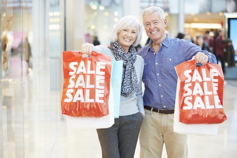 Bärande påsar för lyckliga höga par i shoppinggalleria arkivbild