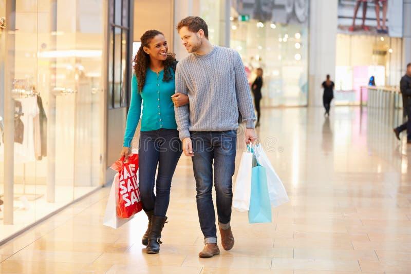 Bärande påsar för lyckliga par i shoppinggalleria royaltyfri bild