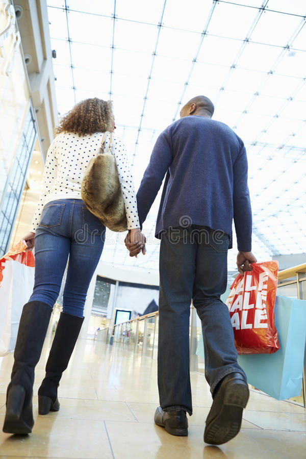 Bärande påsar för lyckliga par i shoppinggalleria arkivbilder