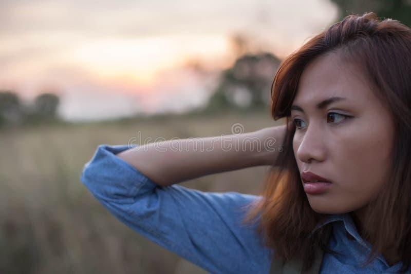 Bärande påse för kvinna av handelsresande i fältsolnedgångarna royaltyfri fotografi
