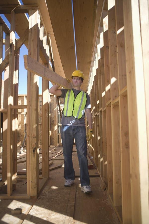 Bärande planka för jobbare av trä royaltyfri foto