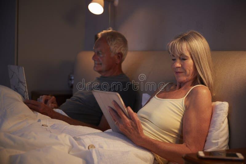 Bärande pyjamas för höga par som ligger i säng genom att använda Digital apparater royaltyfria foton