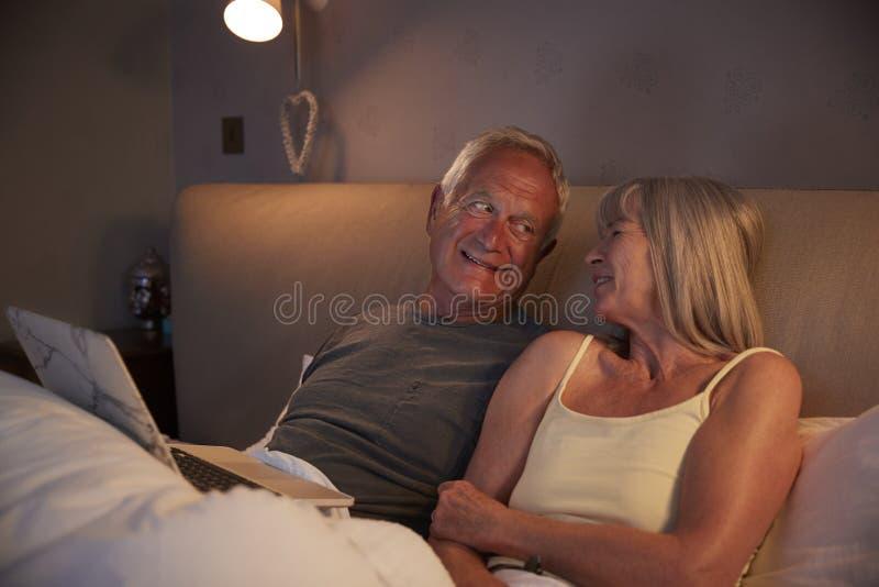 Bärande pyjamas för höga par som ligger i säng som ser bärbara datorn royaltyfri foto