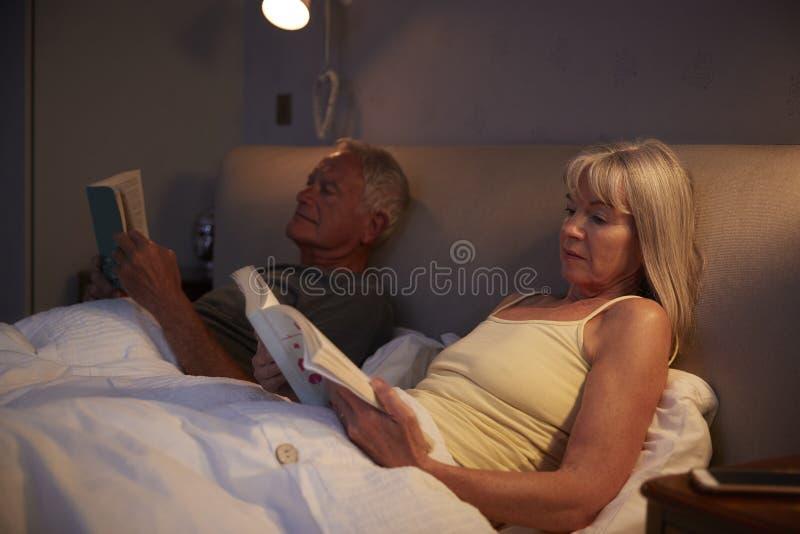 Bärande pyjamas för höga par som ligger i sängläsning arkivfoton