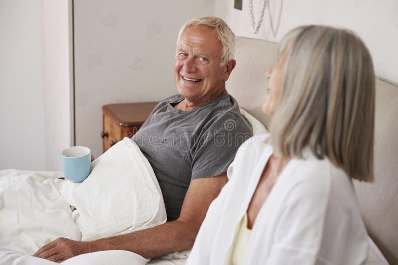 Bärande pyjamas för pensionerade par som sitter i säng som dricker te royaltyfri foto