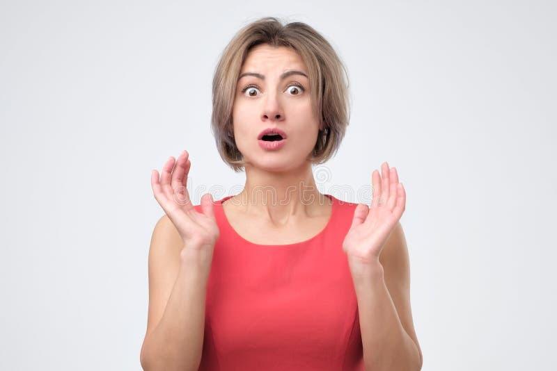 Bärande röd klänning för förvånad chockad kvinnlig och att hålla upp hennes hand och att öppna munnen royaltyfria foton