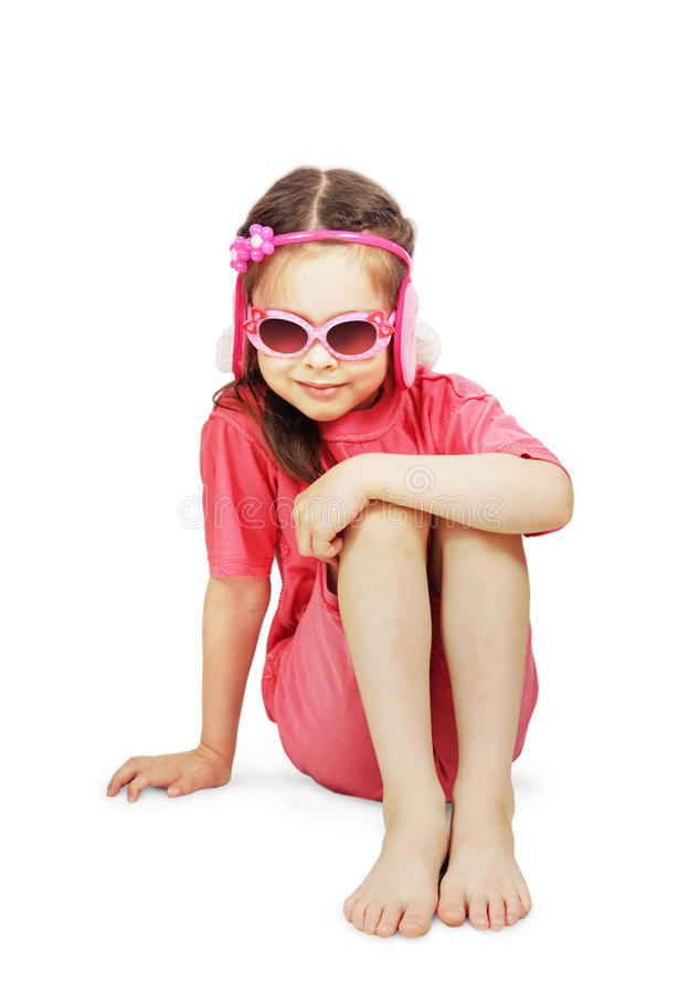 Bärande rosa färgkläder för liten gullig flicka med sitta för solglasögon royaltyfria bilder