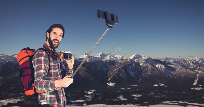 Bärande ryggsäck för Hipster med kameran och taselfie, medan stå mot berg arkivbild