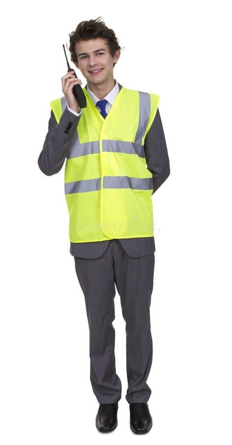 Bärande säkerhetsomslag för man som talar på den Walkie talkien royaltyfri foto