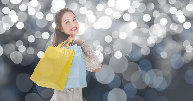 Bärande shoppingpåsar för härlig kvinna över bokeh arkivbilder