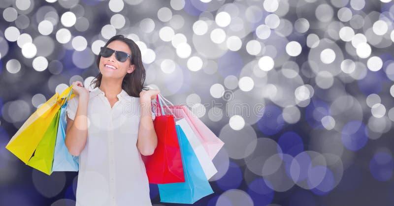 Bärande shoppingpåsar för lycklig kvinna över bokeh arkivbilder