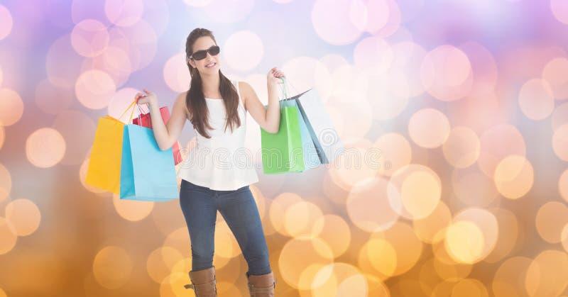 Bärande shoppingpåsar för trendig kvinna över bokeh fotografering för bildbyråer