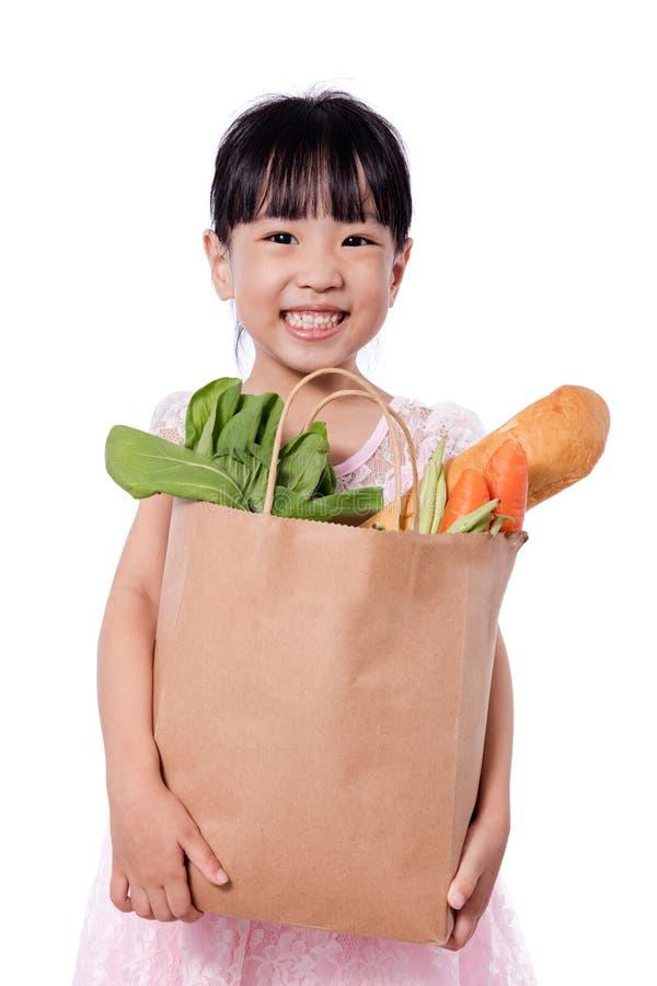 Bärande shoppingpåse för asiatisk liten kinesisk flicka med livsmedel arkivbild