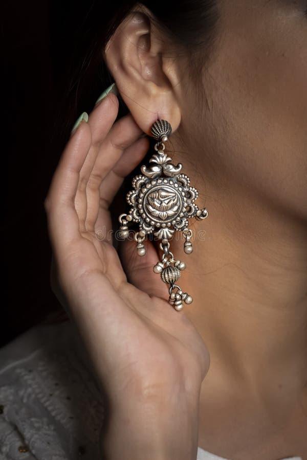 Bärande silverörhänge för kvinna på örat med handvisning royaltyfri foto