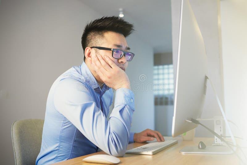 Bärande skjorta Confindent för ung asiatisk affärsman och exponeringsglasarbete, medan sitta framme av den skrivbords- datoren på fotografering för bildbyråer