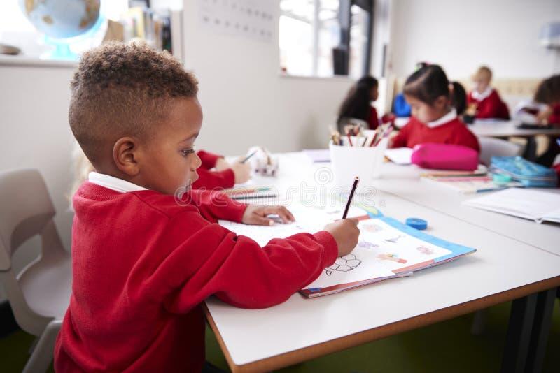 Bärande skolalikformig för ung svart skolpojke som sitter på ett skrivbord i en klassrumteckning för begynnande skola, slut upp,  fotografering för bildbyråer