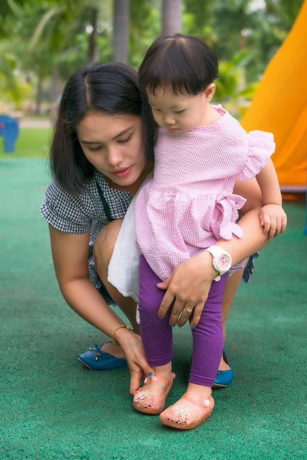 Bärande skor för asiatisk ung moderhjälpdotter royaltyfri fotografi