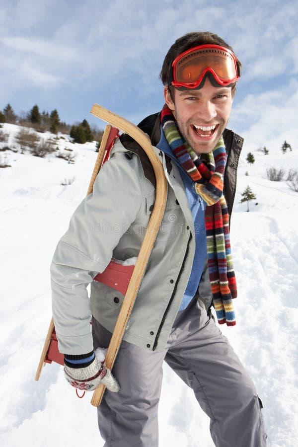 Bärande Sled för ung man i alpin liggande royaltyfri fotografi