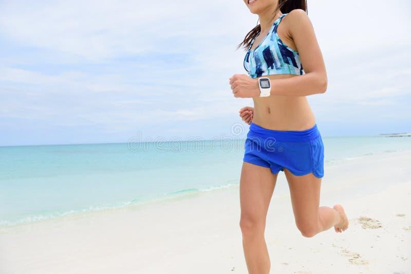 Bärande smartwatch för löparespring på stranden arkivfoto