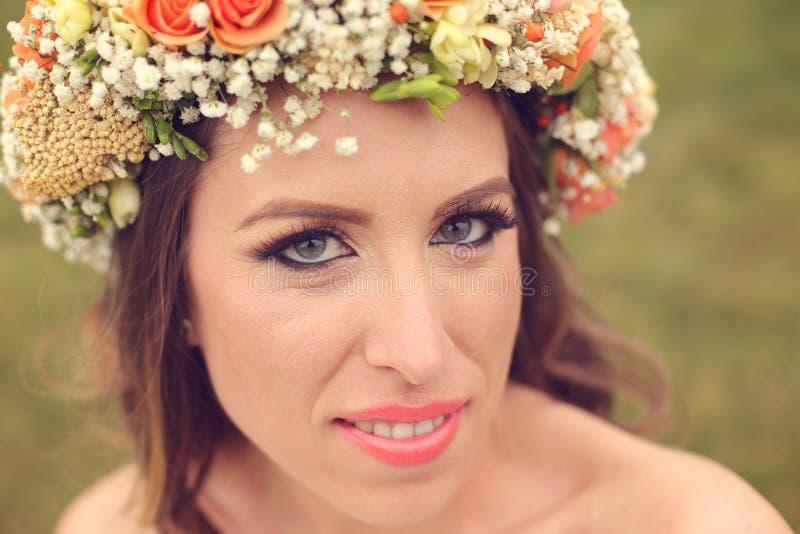 Bärande smink för härlig brud och en blom- krona royaltyfri bild