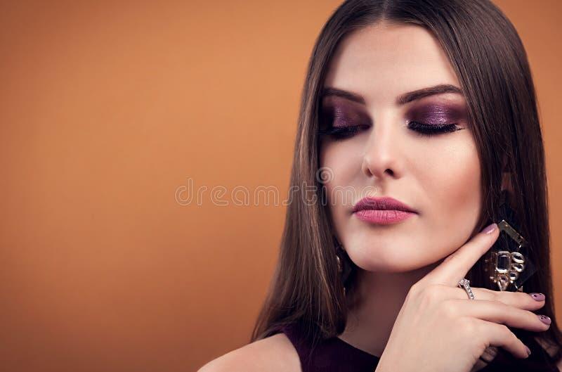 Bärande smycken för härligt smink för kvinna perfekt på brun bakgrund royaltyfria foton