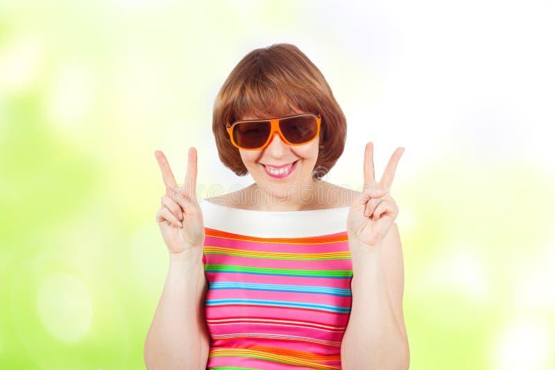 Bärande solglasögon för en gullig flicka och en ljus T-tröja arkivfoton