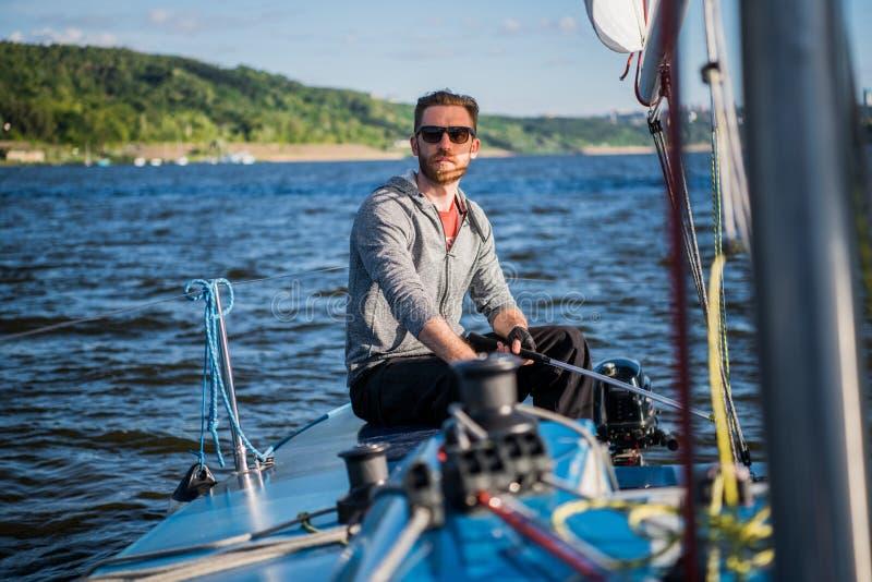 Bärande solglasögon för en man och tillfällig kläder, som han kör en liten jolle runt om en sjö eller en flod royaltyfri foto