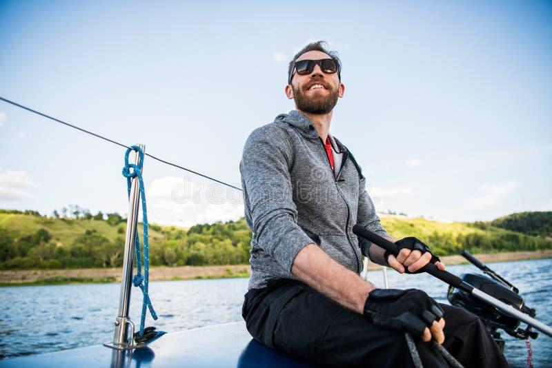 Bärande solglasögon för en man och tillfällig kläder, som han kör en liten jolle runt om en sjö eller en flod arkivfoto