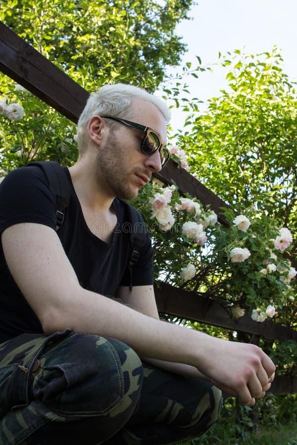 Bärande solglasögon för en ung skäggig man vid staketet av den blommande trädgården Ett grabbsammanträde vid staketet och se ner royaltyfri fotografi