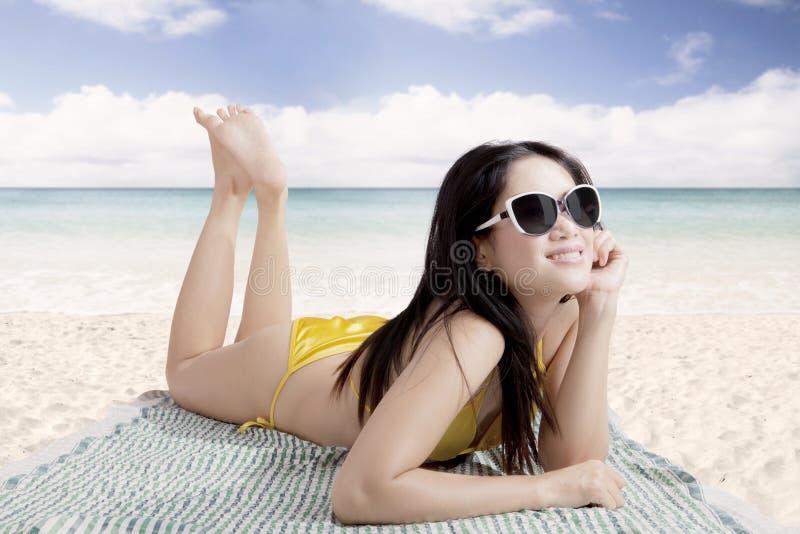 Bärande solglasögon för härlig asiatisk kvinna som solbadar i bali arkivbilder
