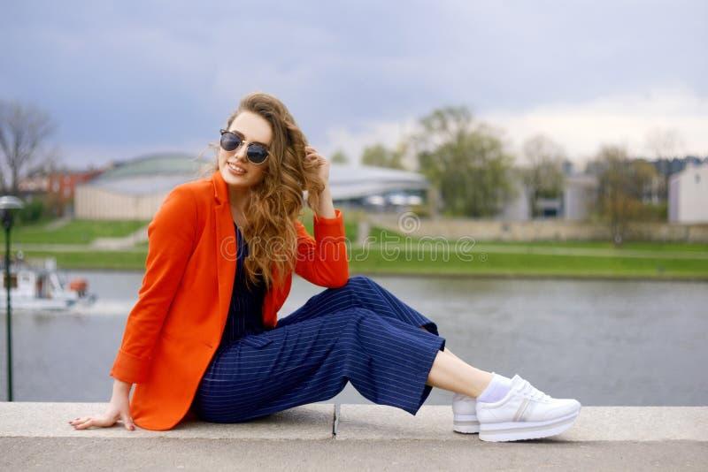 Bärande solglasögon för härlig flicka på flodstranden Flickasammanträde på pir och lookingat floden Härliga unga flickor utomhus arkivbilder