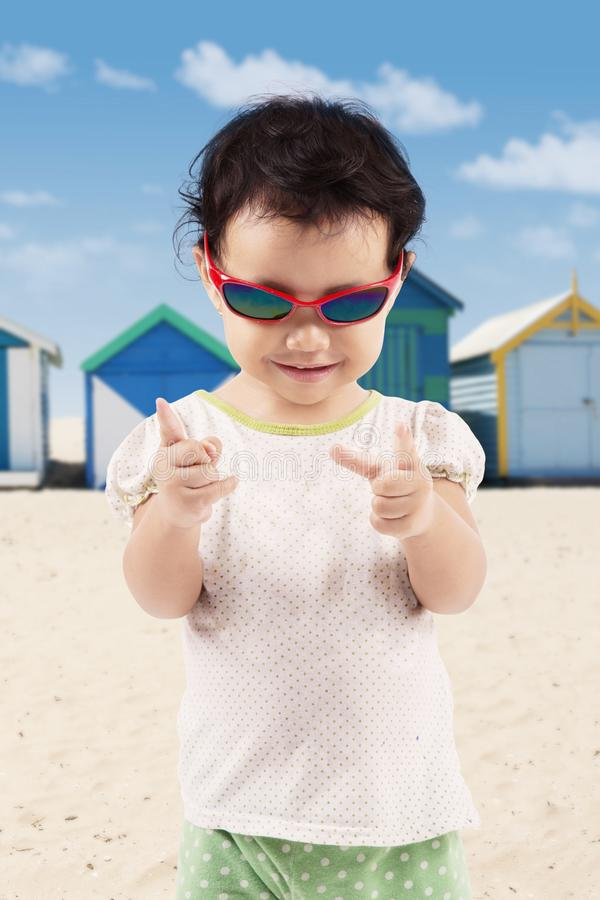 Bärande solglasögon för lycklig liten flicka på stranden fotografering för bildbyråer