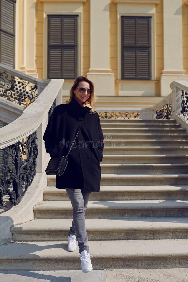 Bärande solglasögon för moderiktig kvinna som går ner ett yttre flyg av stentrappa arkivbild