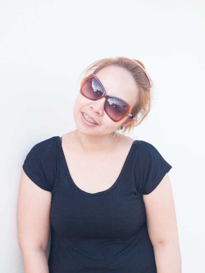 Bärande solglasögon för ung asiatisk dam som ler i natur royaltyfria bilder