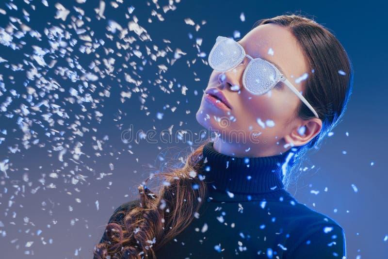 Bärande solglasögon för ung kvinna som täckas i frost som under står royaltyfri fotografi