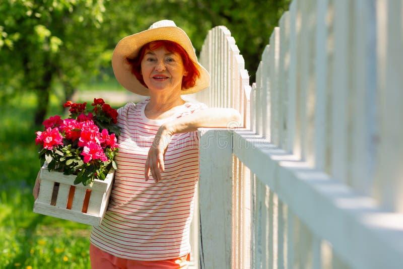 Bärande sommarhatt för åldrig kvinna som rymmer trevliga rosa blommor arkivfoton
