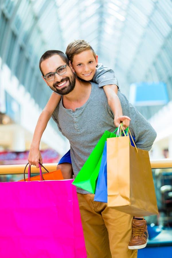 Bärande son för farsa på ryggen i shoppinggalleria royaltyfri fotografi