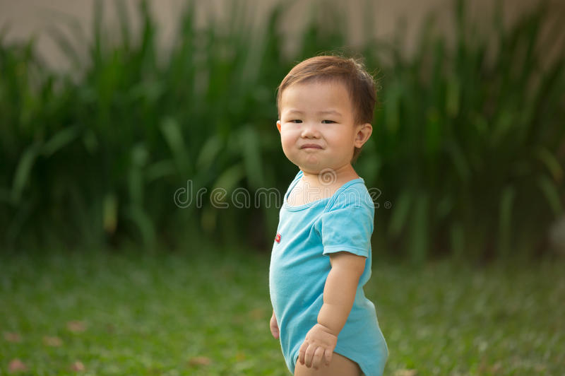 bärande sparkbyxor för 1 åriga kinesiska asiatiska pojke i en trädgård arkivfoton