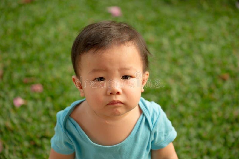bärande sparkbyxor för 1 åriga kinesiska asiatiska pojke i en trädgård royaltyfria foton