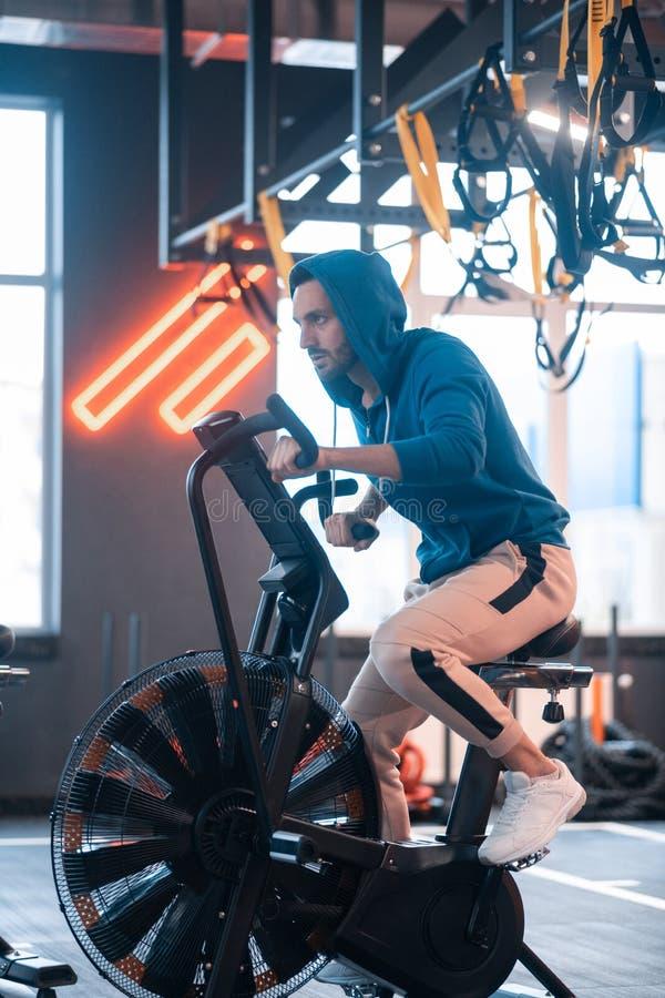 Bärande sportkläder för stilig affärsman som cyklar i idrottshall arkivfoton